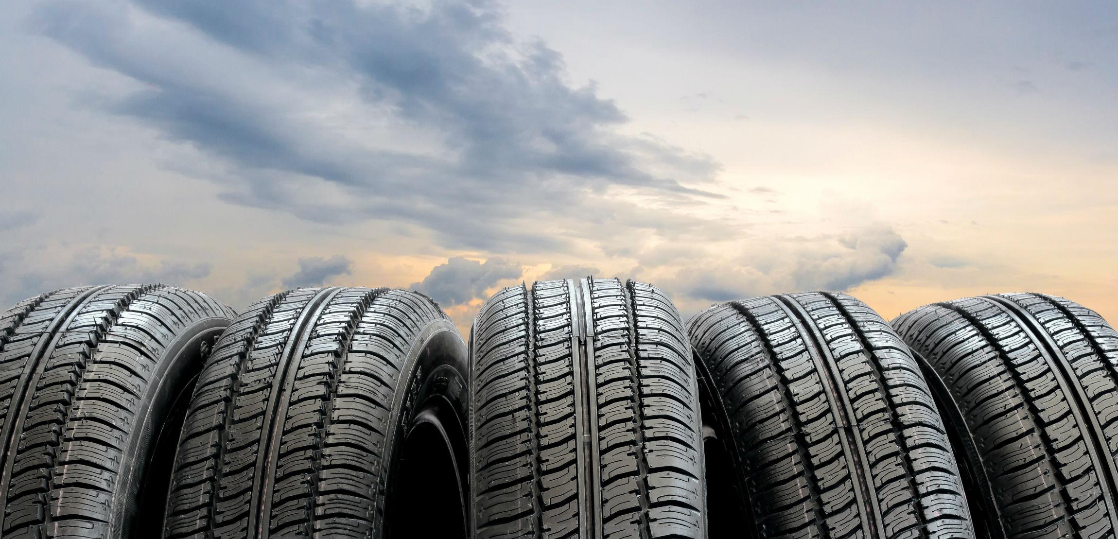 Imagem mostra três bandas de pneus lado a lado com um céu ao fundo