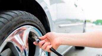 Homem faz a calibragem dos pneus com a ponta do compressor no bico