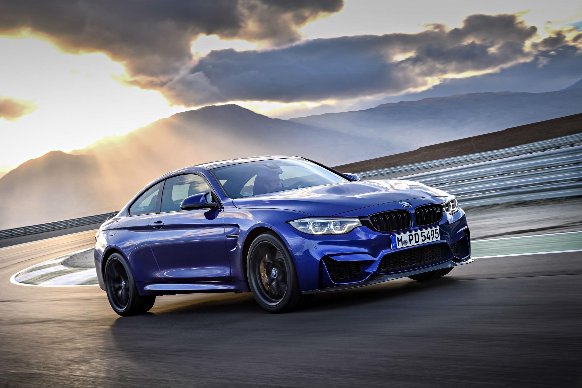 BMW M4 azul na saída de uma curva em movimento em um autódromo