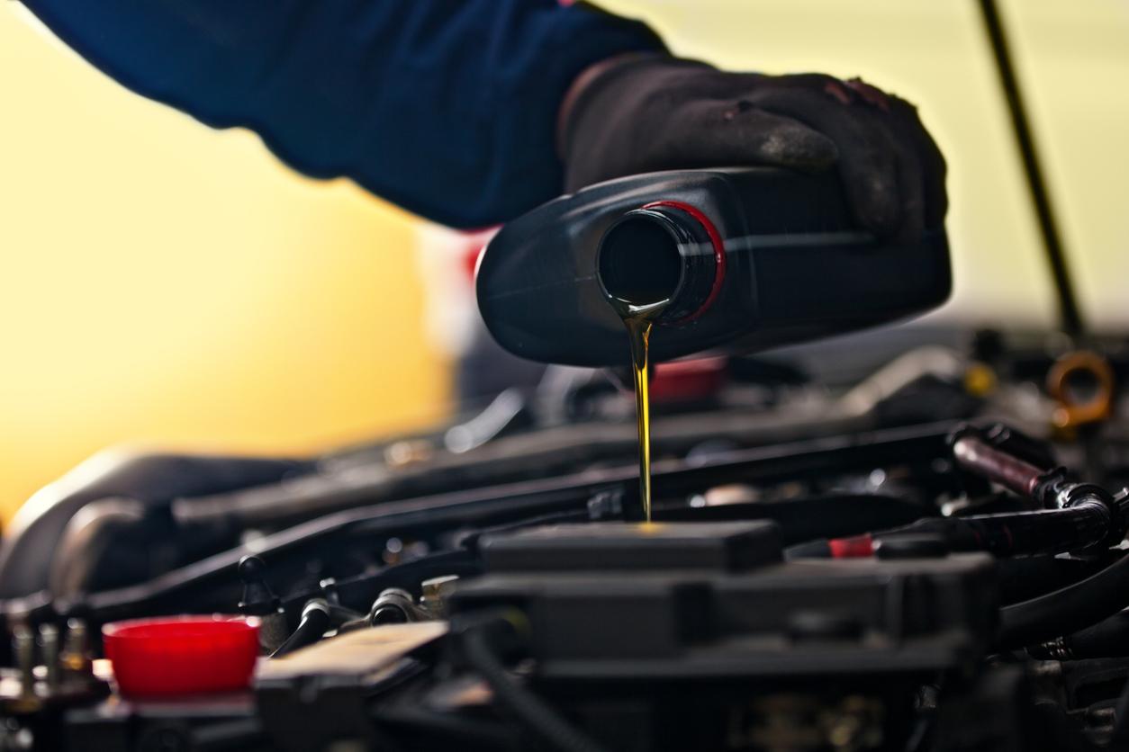 Quando trocar o óleo do carro: imagem mostra uma mão colocando óleo no motor