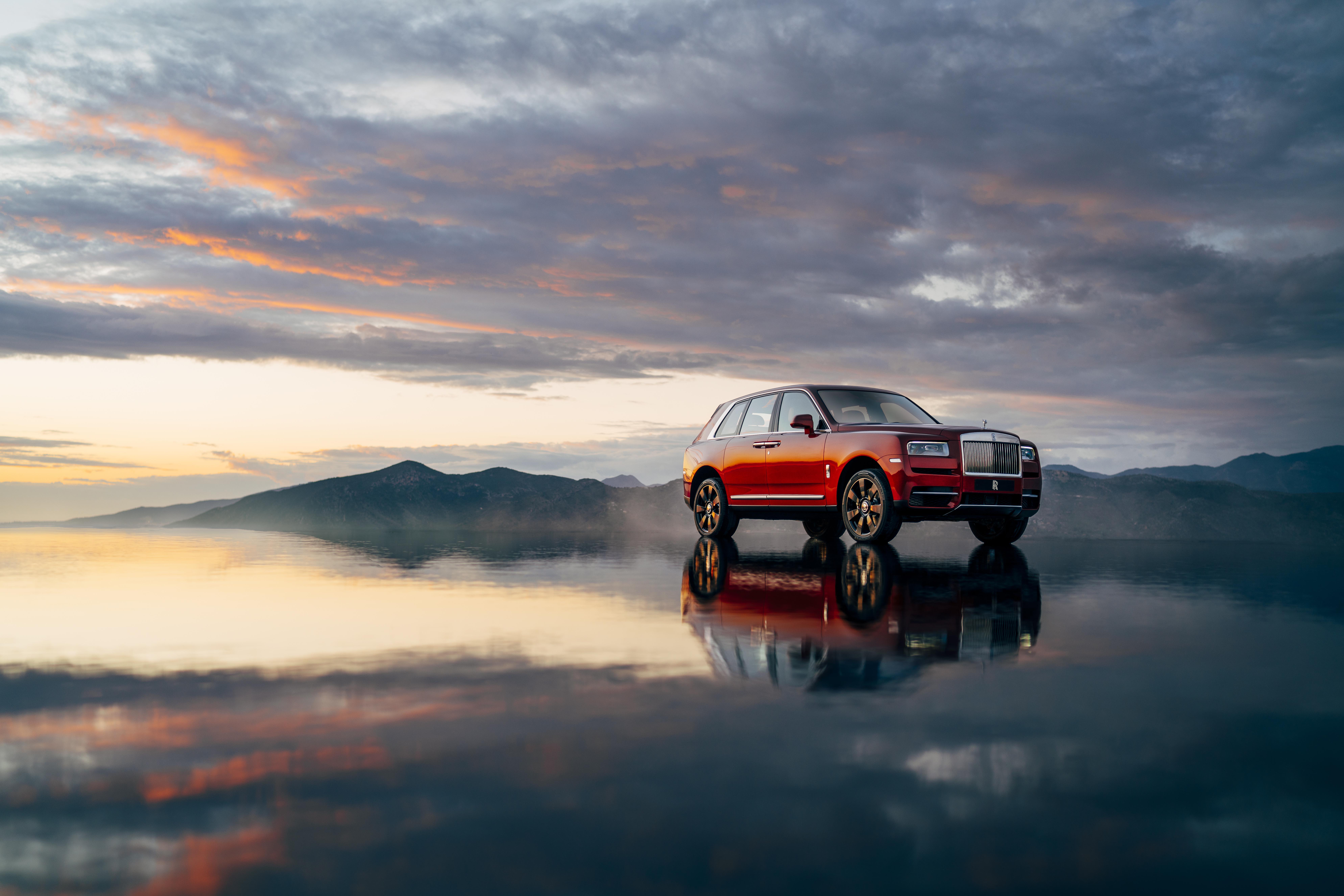 Utilitário esportivo Rolls-Royce Cullinan na cor laranja em um chão molhado com reflexo do carro e do céu e montanhas ao fundo no entardecer