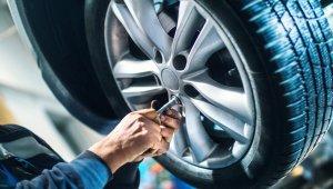 Homem realiza troca de pneu aparafusando as porcas das rodas