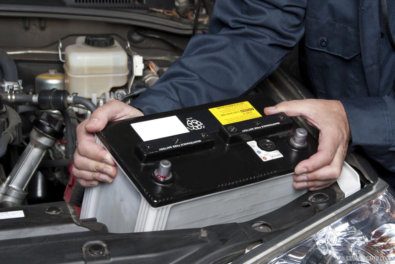 Homem retira a bateria com as mãos do compartimento do motor para realizar a troca