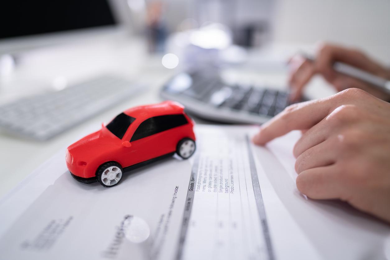 Homem fazendo contas em calculadora com carro vermelho de brinquedo em cima da mesa
