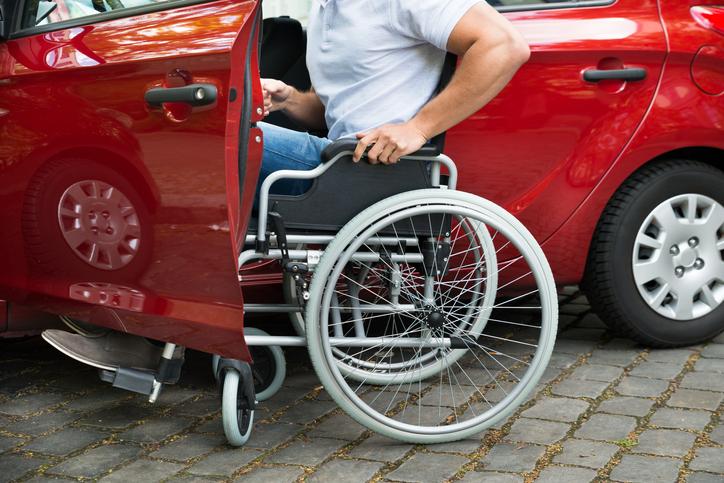 Comprar veículo pcd: homem com deficiência se apoia na cadeira de rodas para entrar em um carro vermelho.
