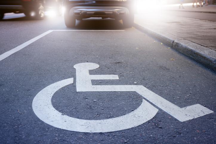 Comprar veículo pcd: símbolo de pessoas com deficiência em vaga de carro na rua