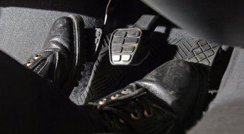 Imagem mostra os pedais do carro, sendo que cada pé está apoiado em um pedal (acelerador e freio)e o da embreagem está em destaque.
