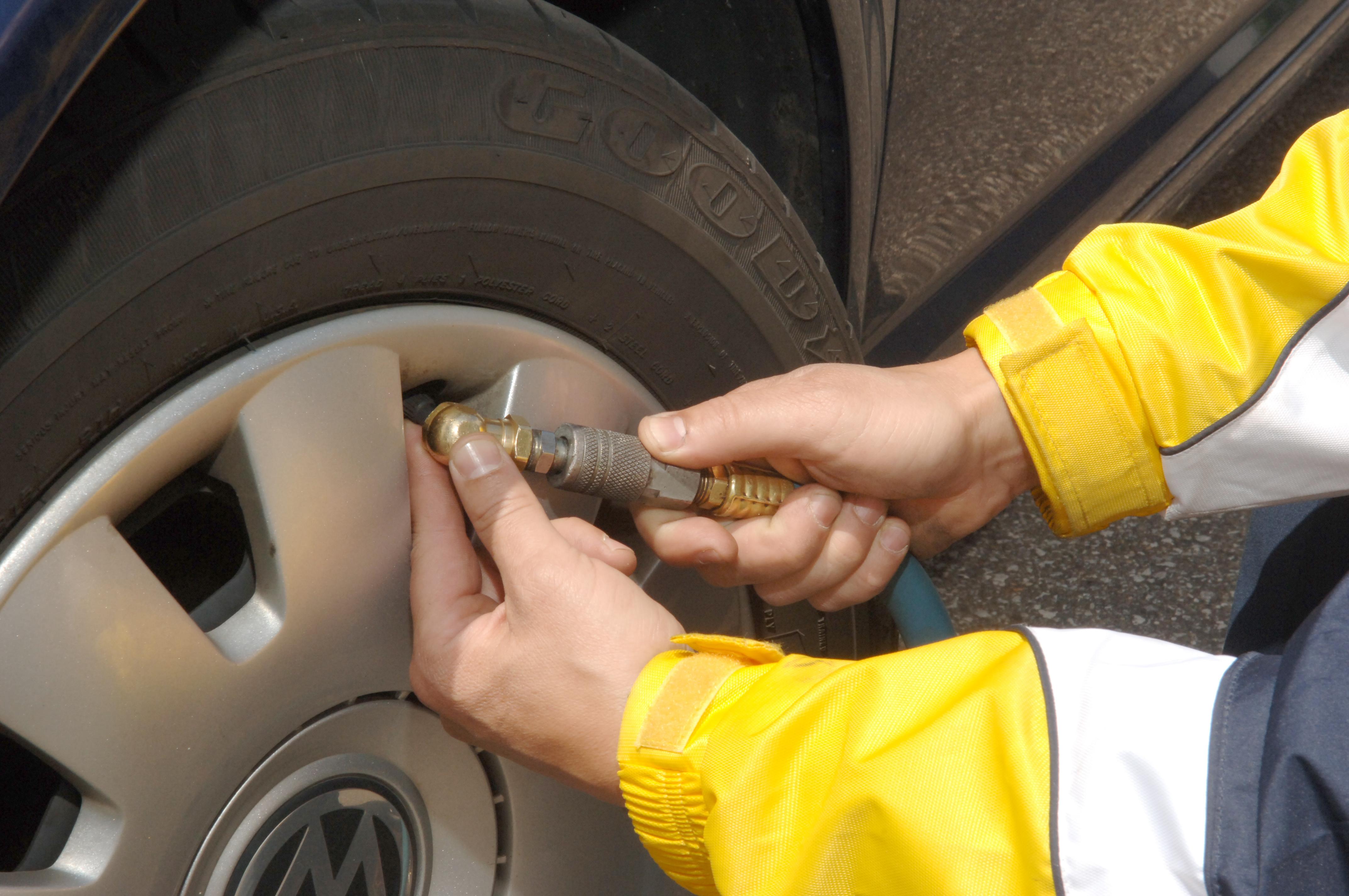 Homem posiciona ponta do compressor no bico do pneu para fazer a calibragem