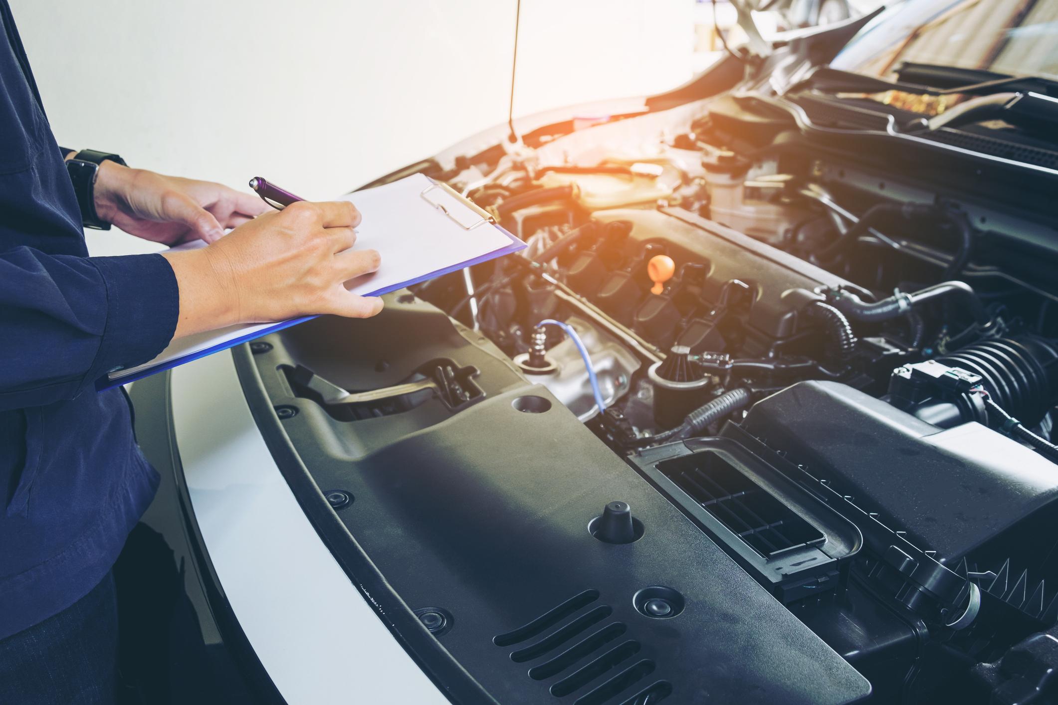Imagem mostra um homem fazendo anotações na prancheta durante a revisão de um carro