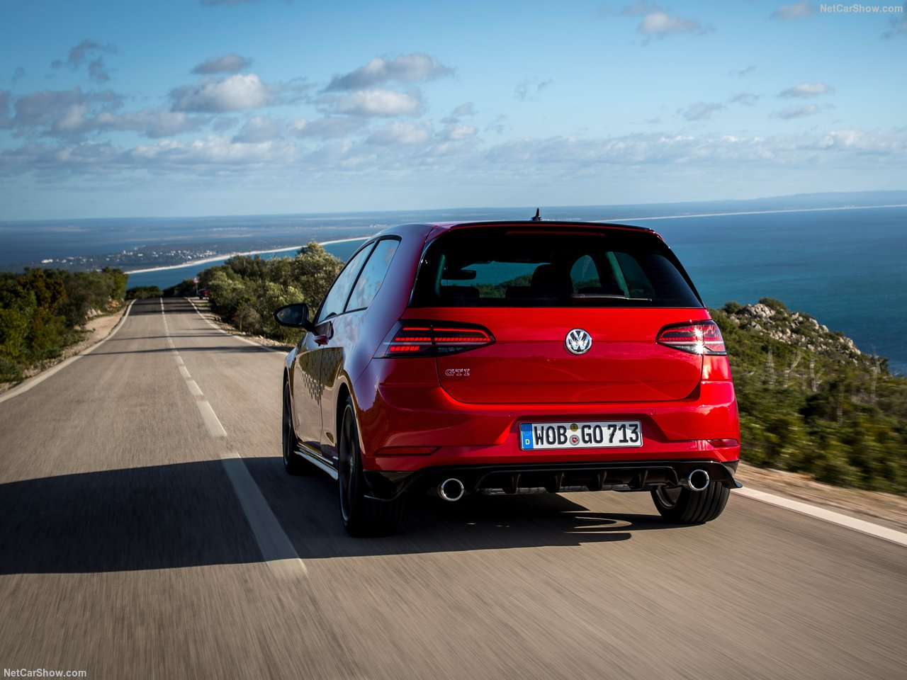Volkswagen Golf GTI vermelho na estrada asfaltada e com céu azul ao fundo