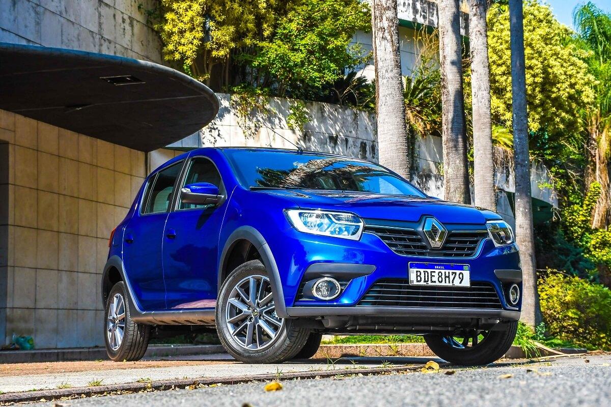 Renault Sandero azul quatro portas, ambientado num fundo ensolarado e repleto de árvores