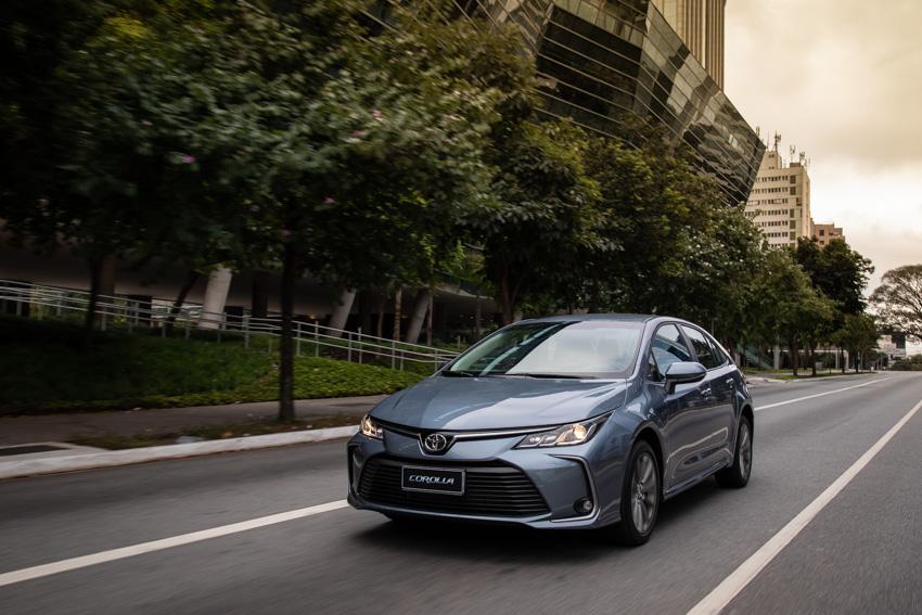 Toyota Corolla azul claro de frente em movimento com sua nova grade fina e faróis pontiagudos
