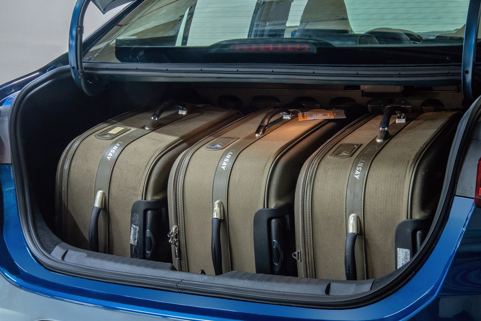 Porta-malas aberto mostra três malas grandes acomodadas no espaço