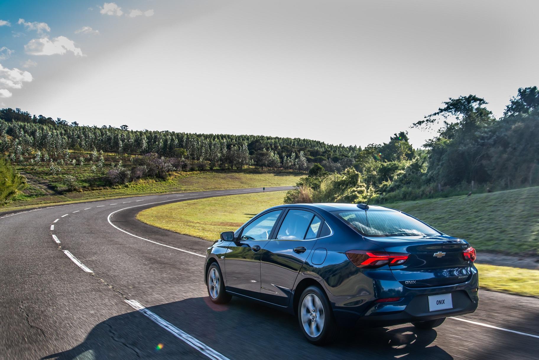 Novo Onix Plus Premier azul visto de traseira em movimento. Carro passará por recall