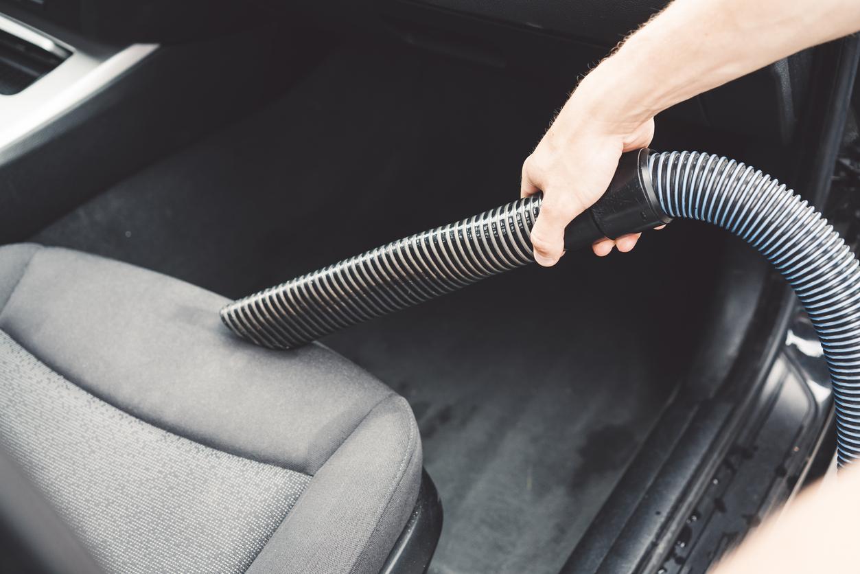 Pessoa passando aspirador de pó nos bancos do carro como limpar banco do carro