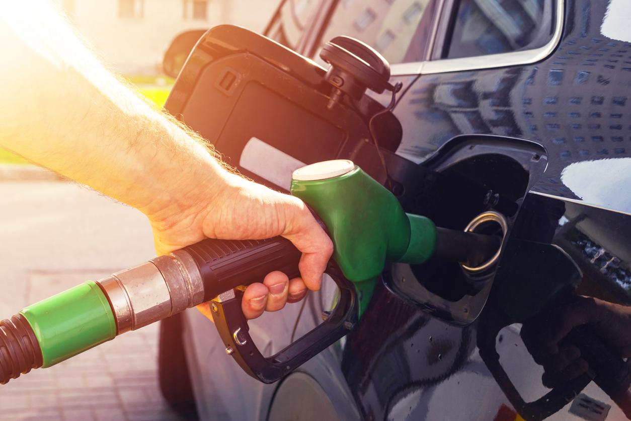 Mão aparece segurando a pistola da bomba de combustível enquanto abastece um carro