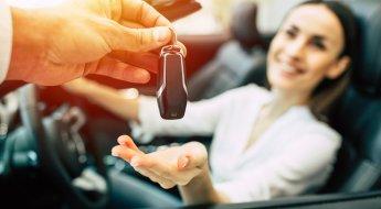 mulher sorrindo dentro do carro enquanto recebe a chave do automóvel