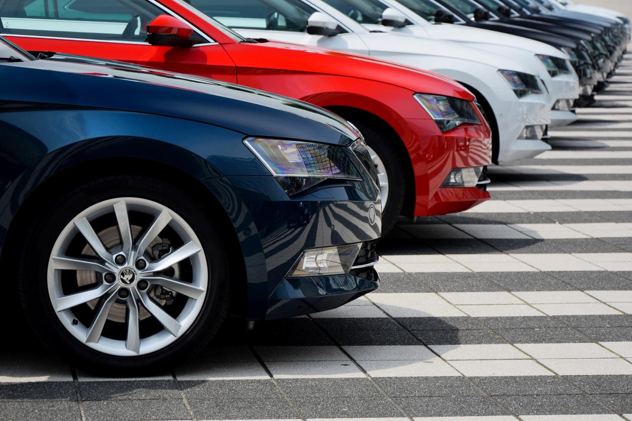 dianteira de vários carros novos enfileirados em um estacionamento