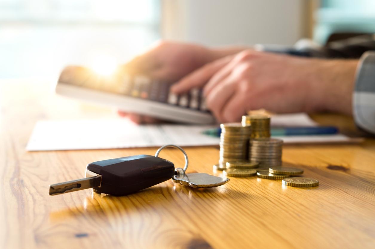 chave de carro e moedas à frente, em cima de uma mesa, e, ao fundo, um homem usando a calculadora