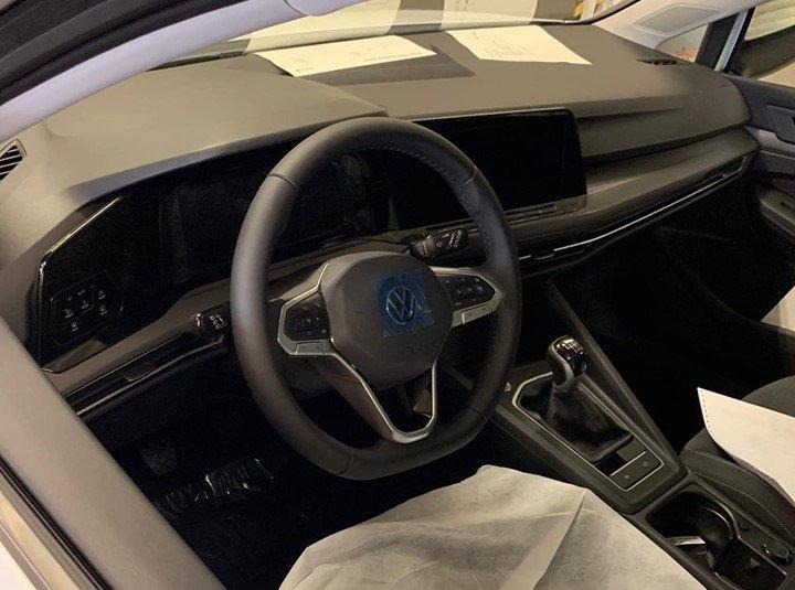 Cabine do Volkswagen Golf de oitava geração mostra volante igual ao do SUV ATlas, bancos cobertos, painel com muito plástico e centrl multimídia grande