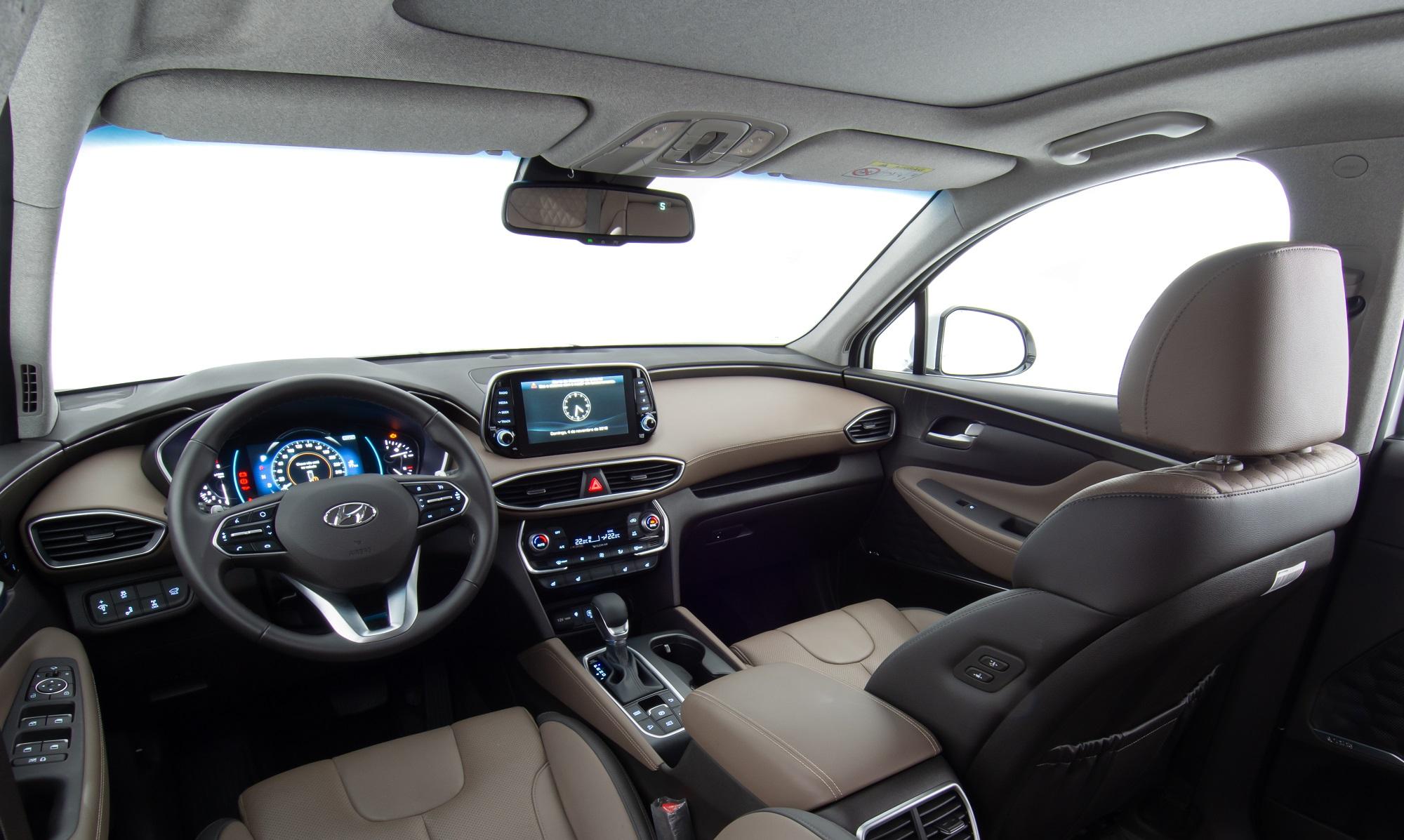 Cabine do novo Santa FE tem bancos de couro marrom com costuras aparentes, tela da cenral multimídia no alto do painel e volante com quatro raios