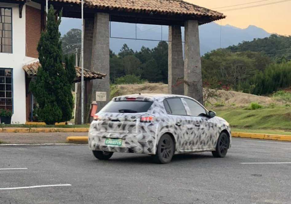 Novo Peugeot 208 camuflado em movimento visto de traseira 3/4