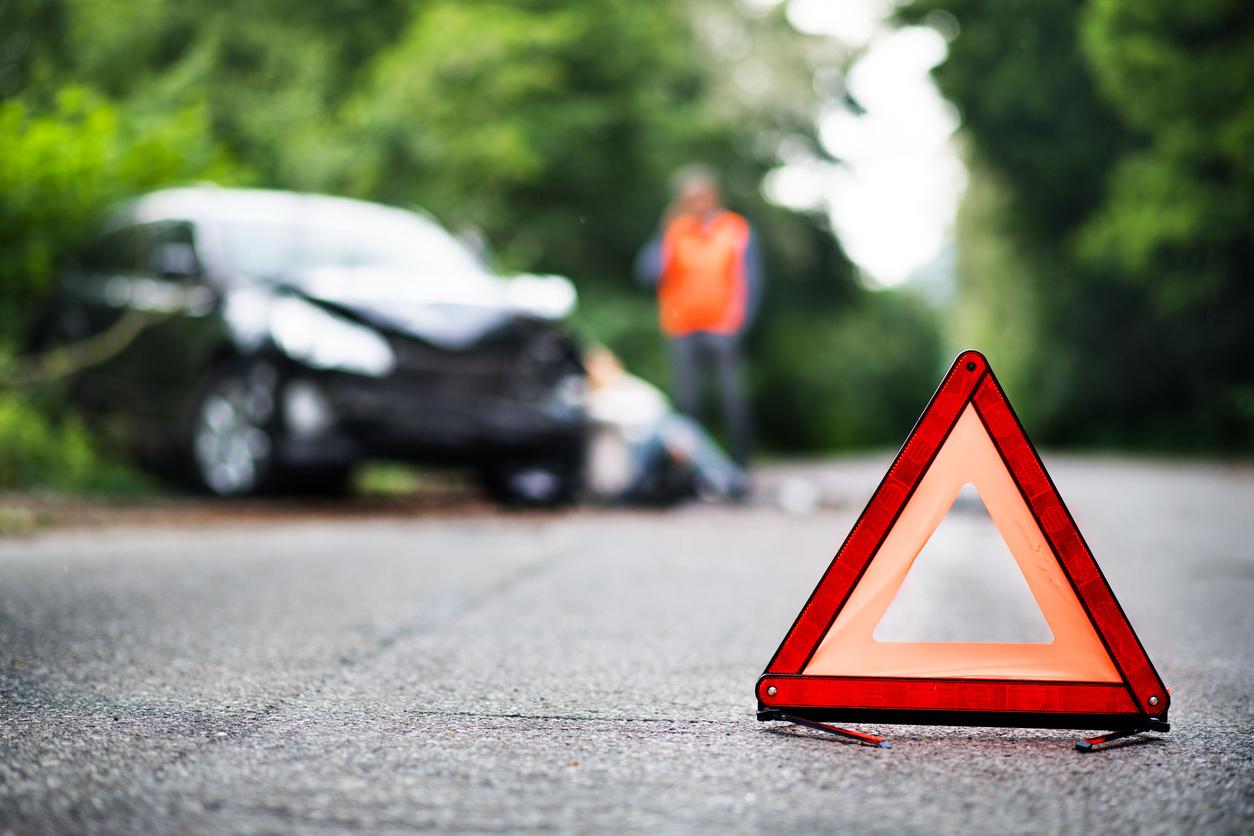 Triângulo na estrada e ao fundo um carro batido