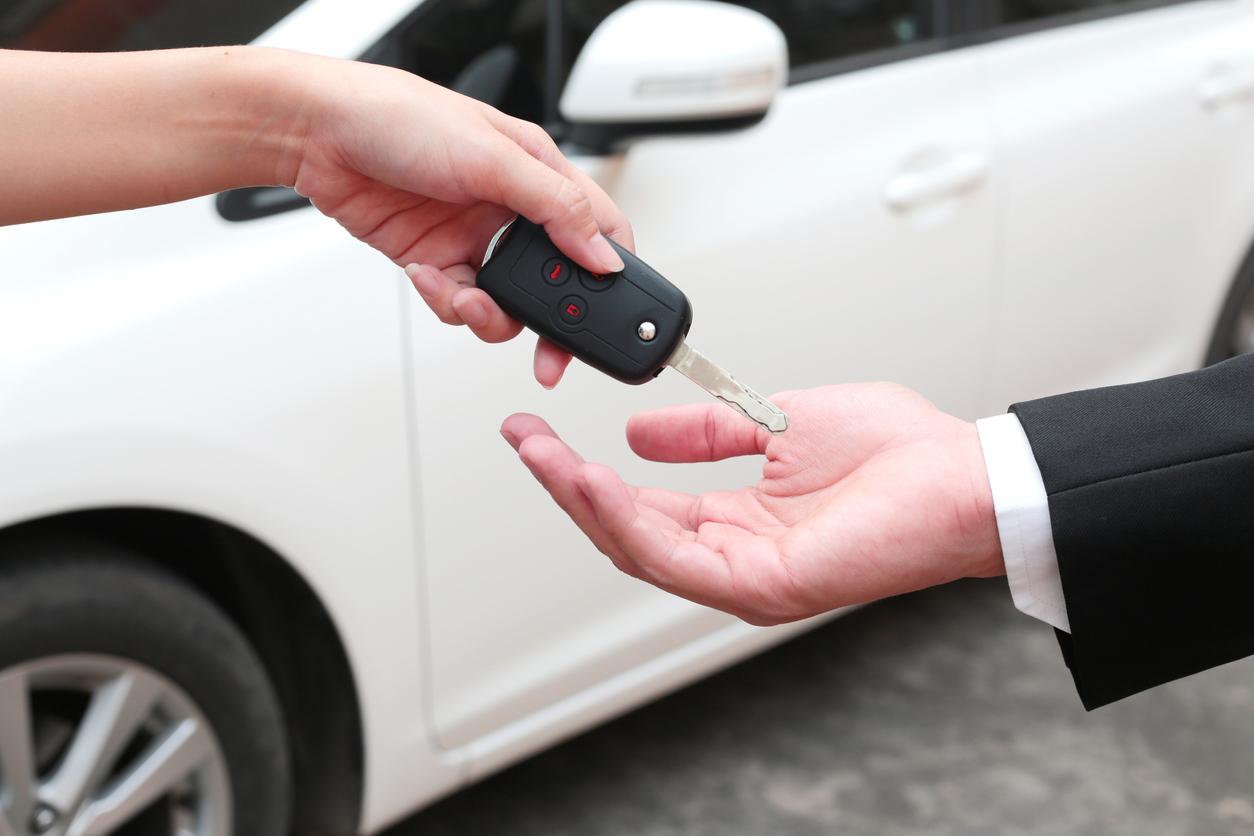 Homem enrega chave a comprador do seu carro