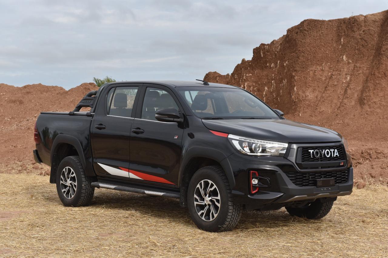 Toyota Hilux GR-S preta em um terreno arenoso parada na cor preta com detalhes discretos em branco e vermelho