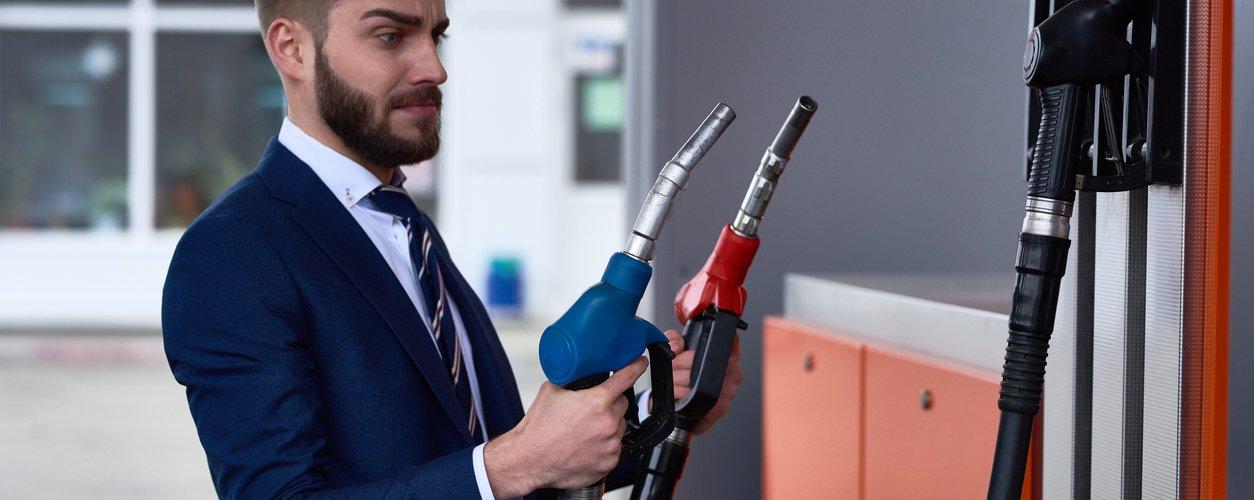 Homem segura duas pistolas de abastecimento na bomba de combustível