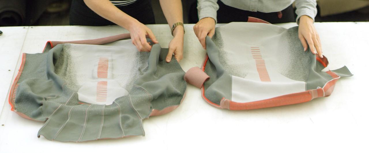 Funcionários manipulam tecido de banco sem costura confeccionado em 3D