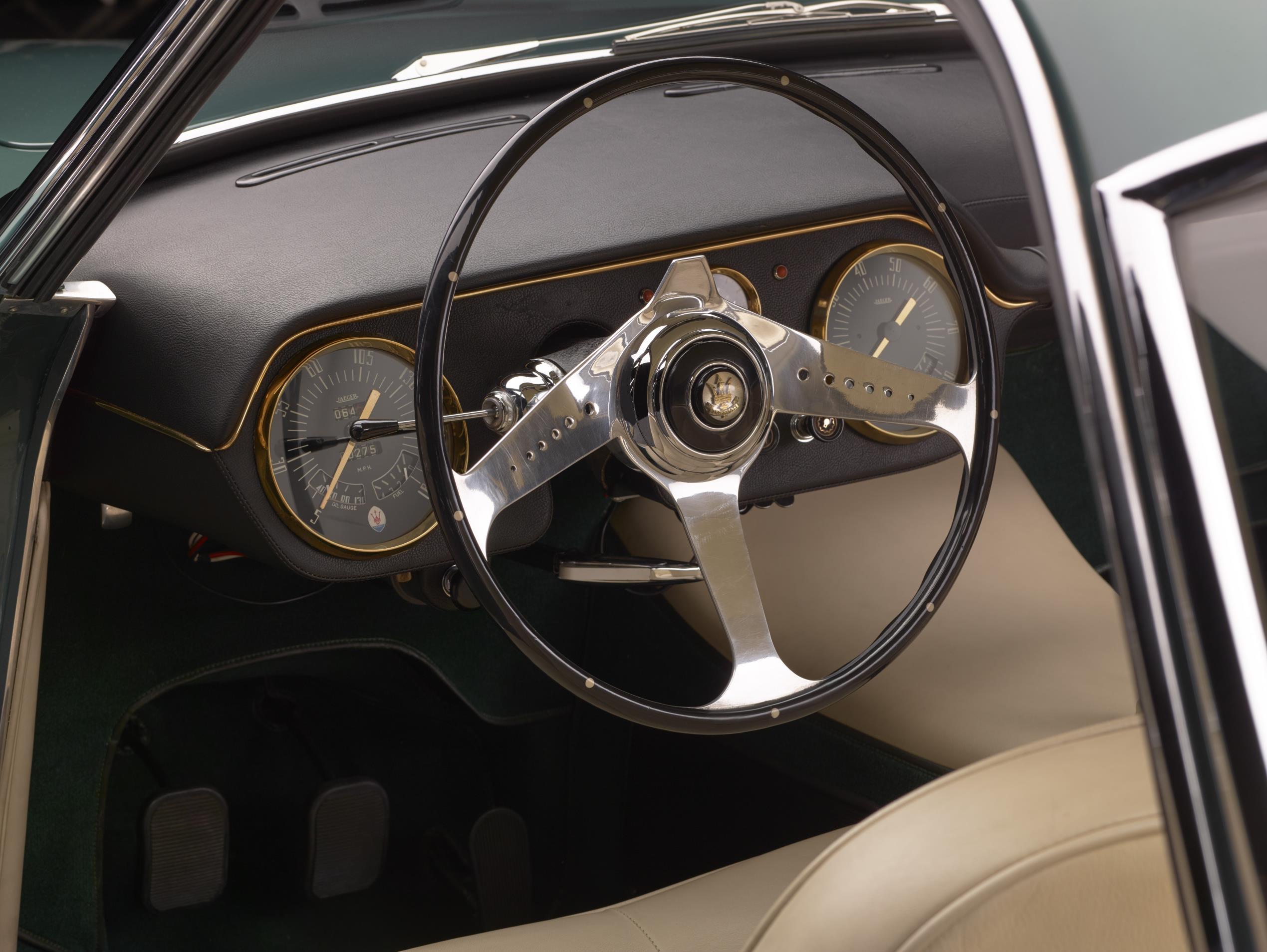 Cabine do Maserati mostra volante de aro fino com três raios cromados e mostradores de instrumentos circulares nas pontas do painel