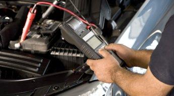 Homem mede a qualidade da bateria do carro com aparelho específico