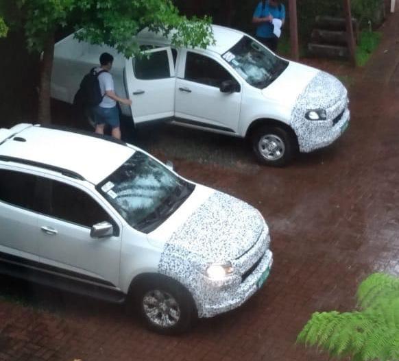 Foto do alto mostra duas picapes S10 brancas com camuflagem na frente e capô e lateral até a metade da altura das caixas de rodas