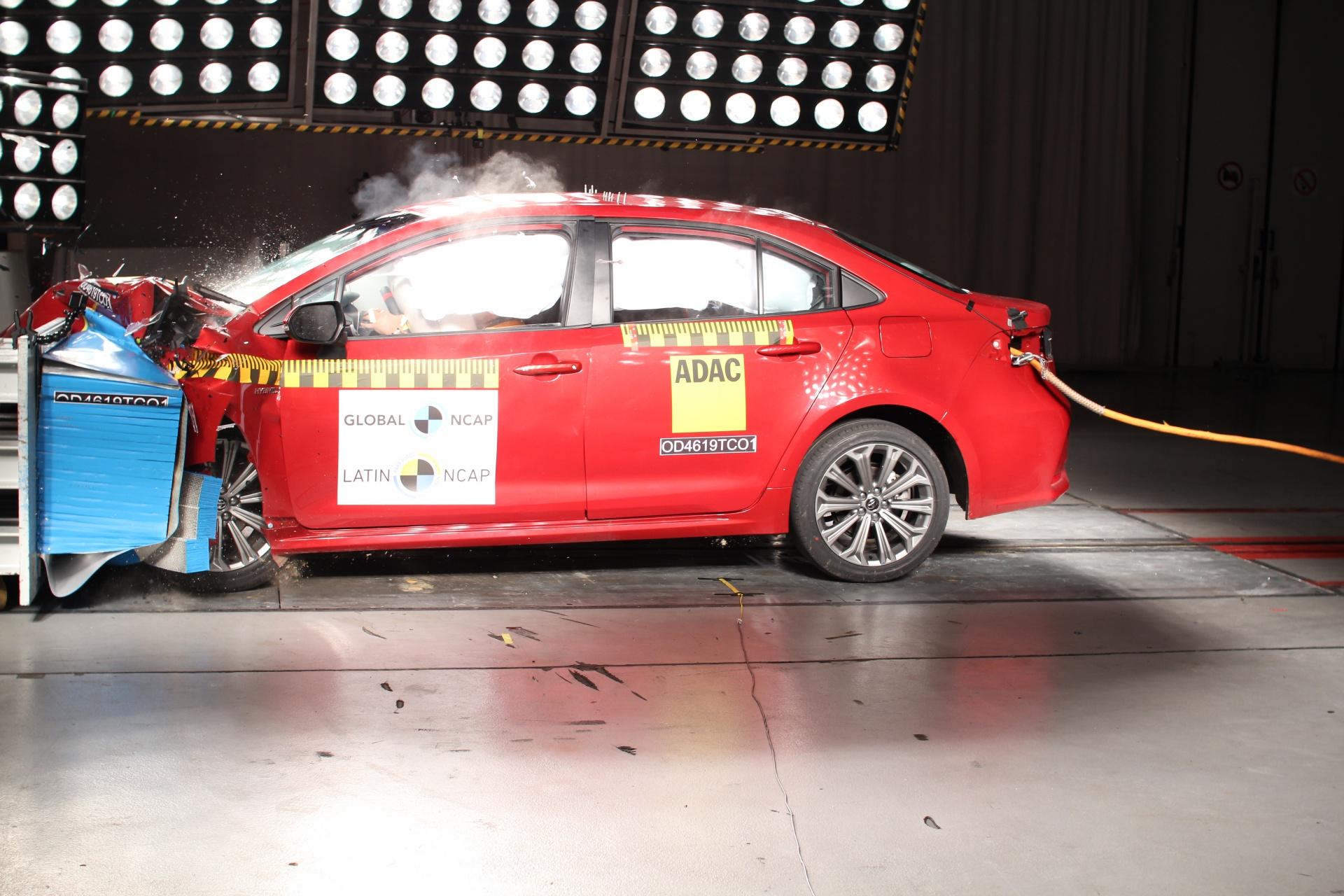 Toyota Corolla vermelho se choca com a baarreira frontal para avaliação nos testes de colisão