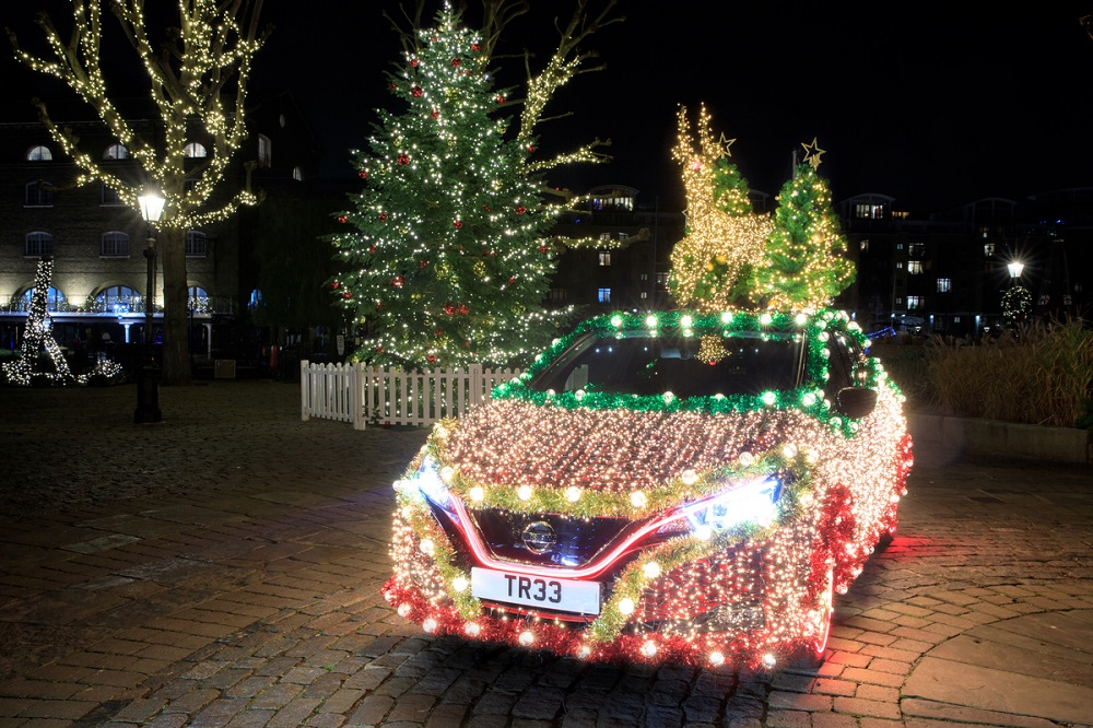 Nissan Leaf cheio de luzes de LEDs e com uma rena iluminada em cima do teto em Paris