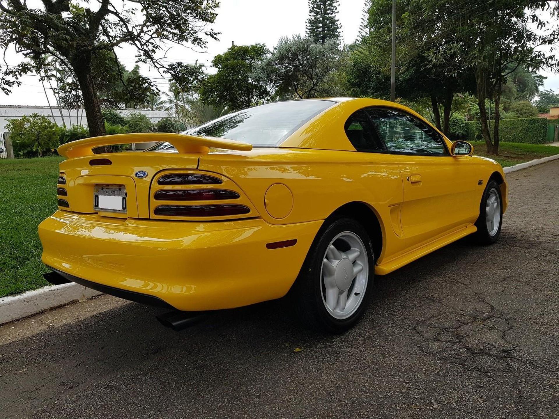 Ford Mustang 5.0 Gt Coupe amarelo visto de traseira com a lanterna em três seções horizontais e aerofólio acima da tampa do porta-malas