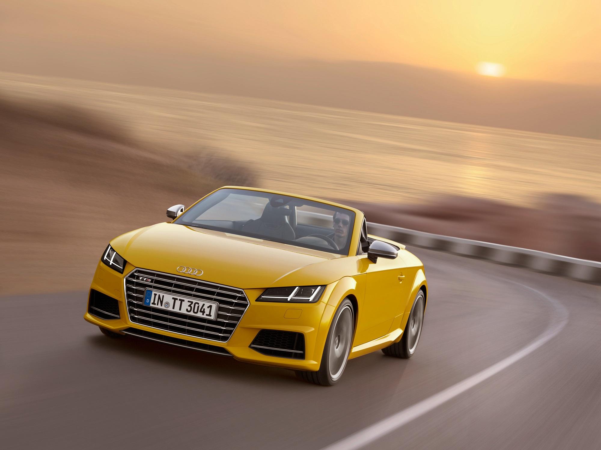 Audi Tt Roadster amarelo em movimento numa estrada de serra com o sol se ponto no horizonte ao fundo