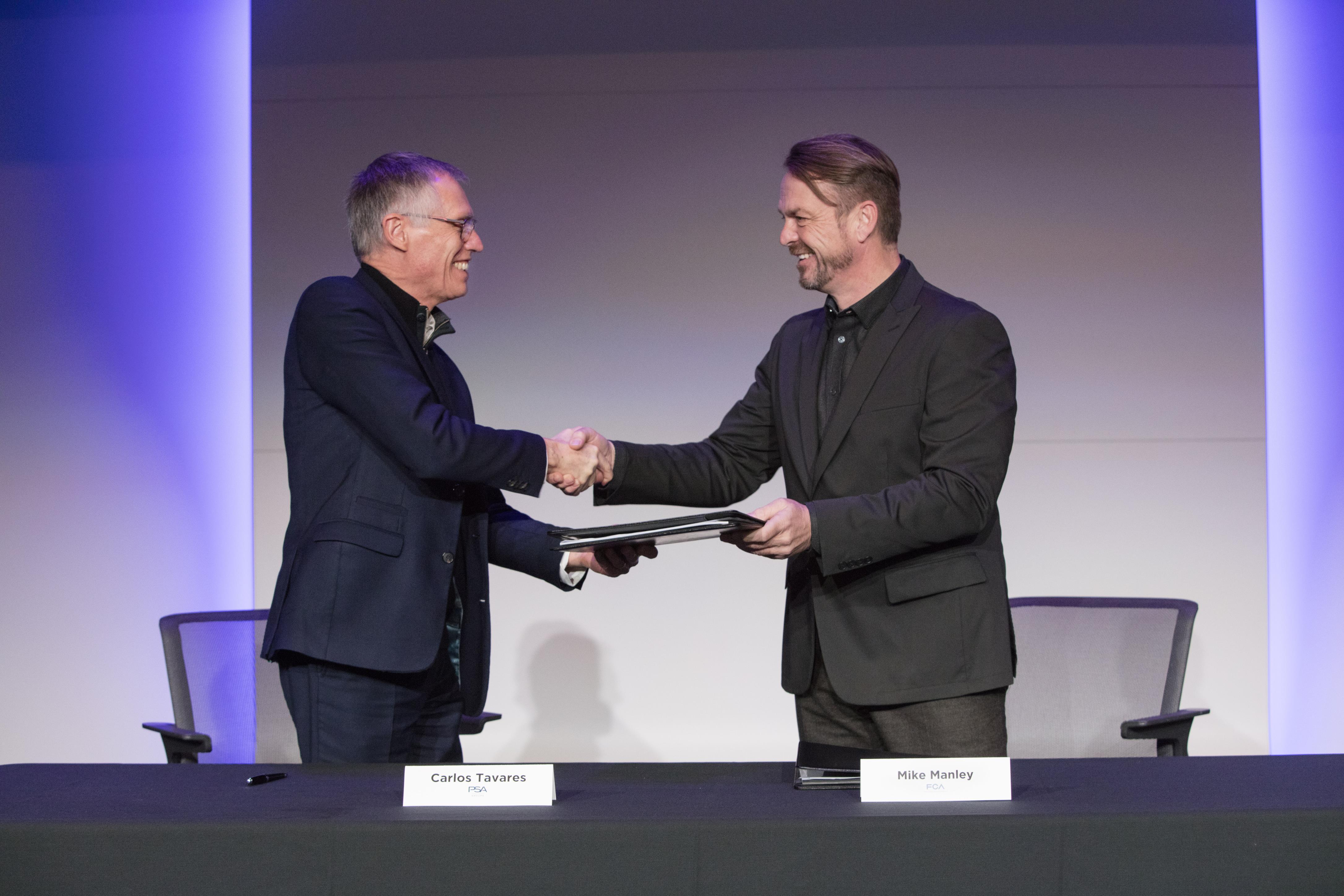 Os presidentes da da PSA, à esquerda, e da FCA, à direita, se cumprimentam durante assinatura do acordo que juntará os dois grupos automotivos