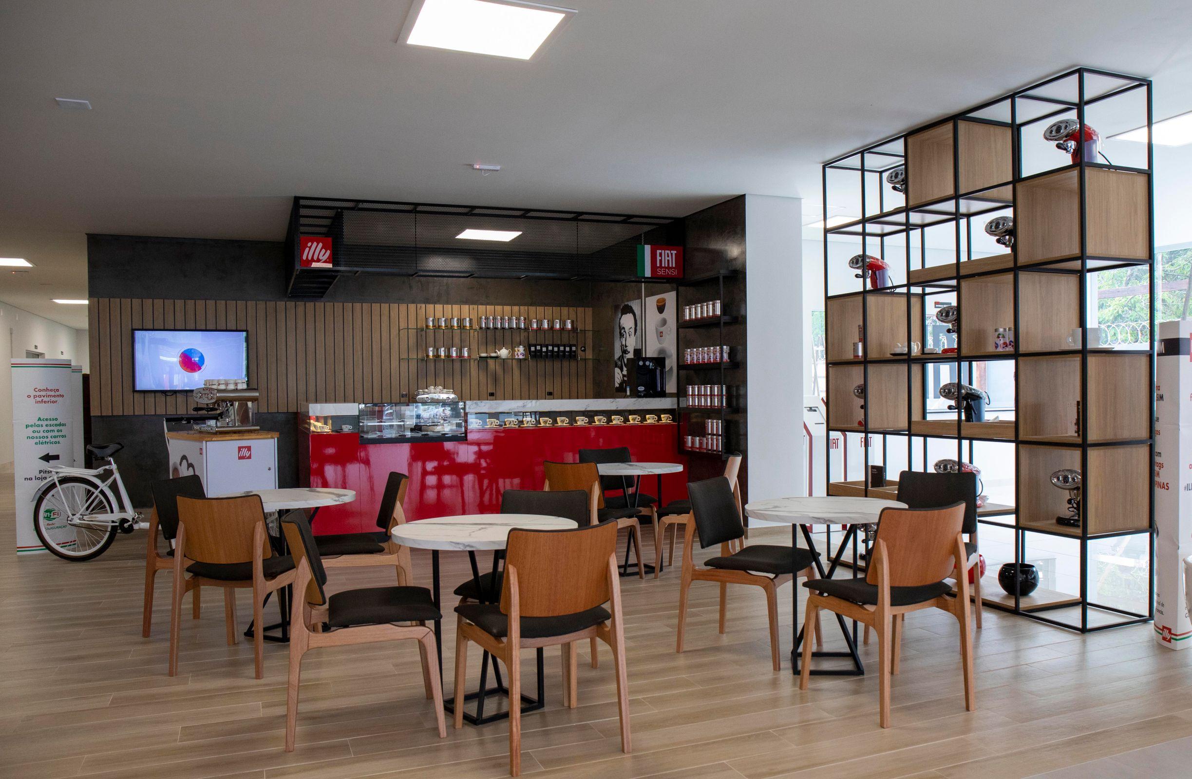 Vista de dentro da concessionária com mesas e cadeiras no espaço coworking e uma cafeteria ao fundo