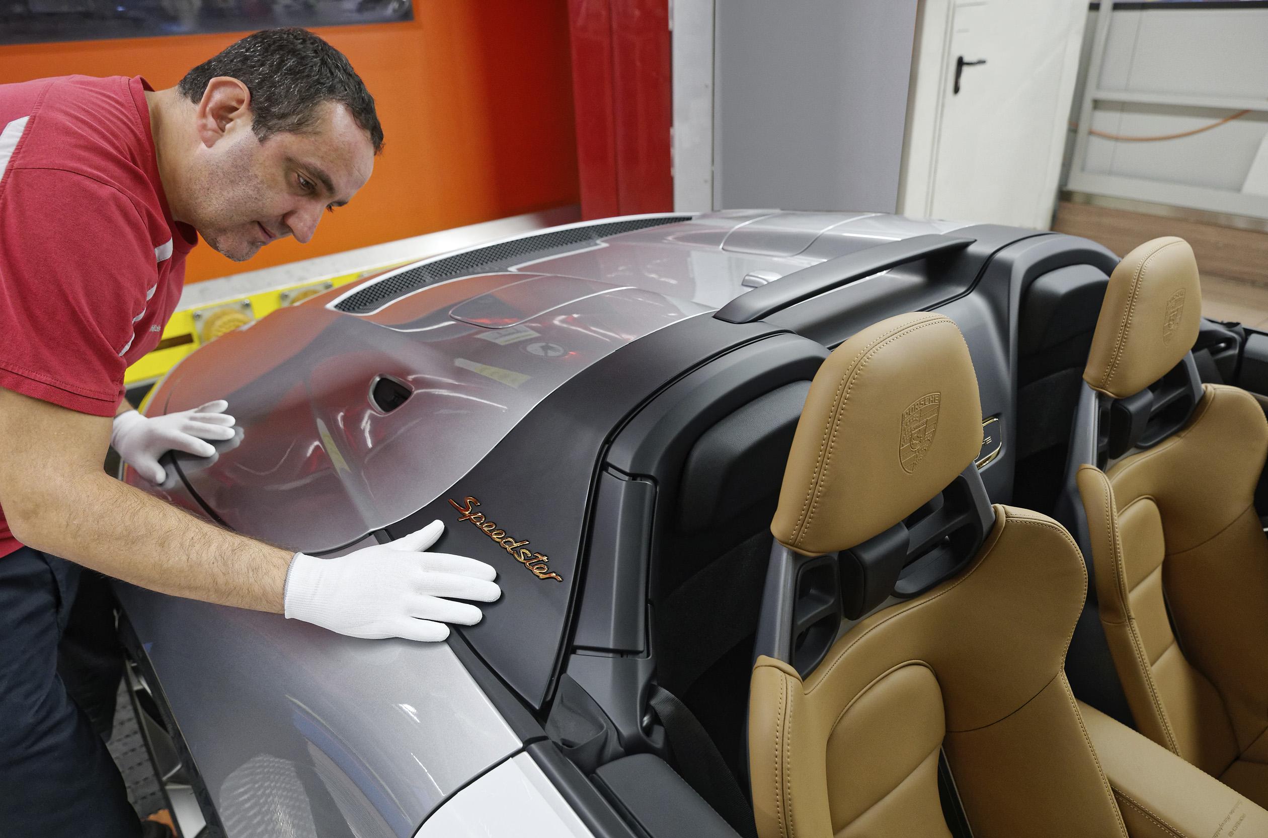 Homem na linha de produção da Porsche exanima, com luvas, a última versão Speedster da sétima geração do 911 a sair de fábrica