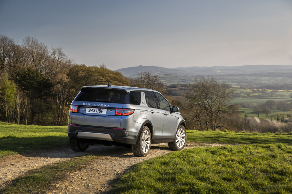 Land Rover Discovery Sport de traseira na cor cinza com lanternas que invadem as laterais e contornos levemente aredondados