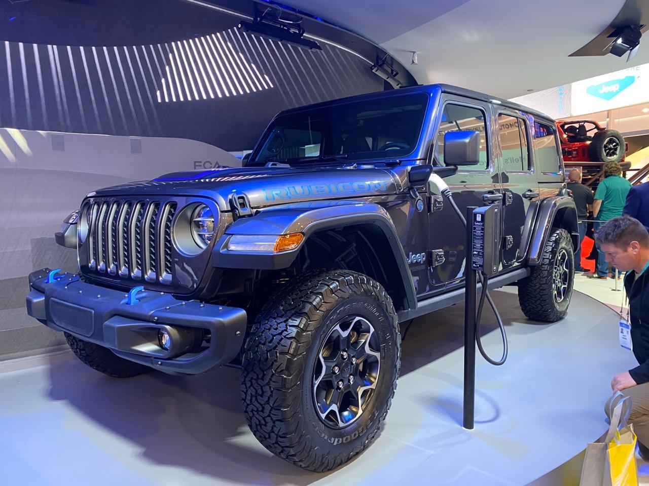 Jeep Wrangler 4xe com mum plugue na tomada próximo ao retrovisor do motorista em exposição no estande da marca na CES