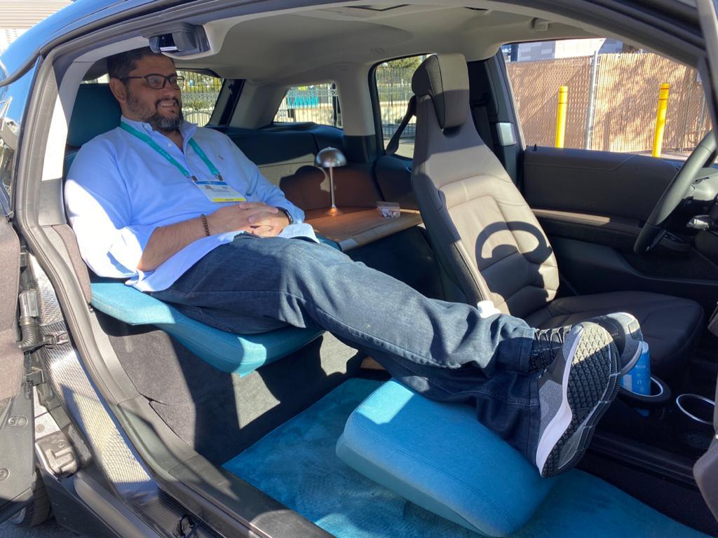 Jornalista sentado na poltrona traseira do i3 limousine e com os pés esticados e pousados no descansa-pé à frente