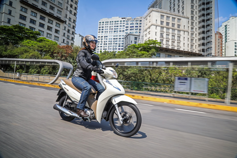 Mulher pilota Honda Biz 2020 em viaduto de São Paulo na cor branca com banco caramelo