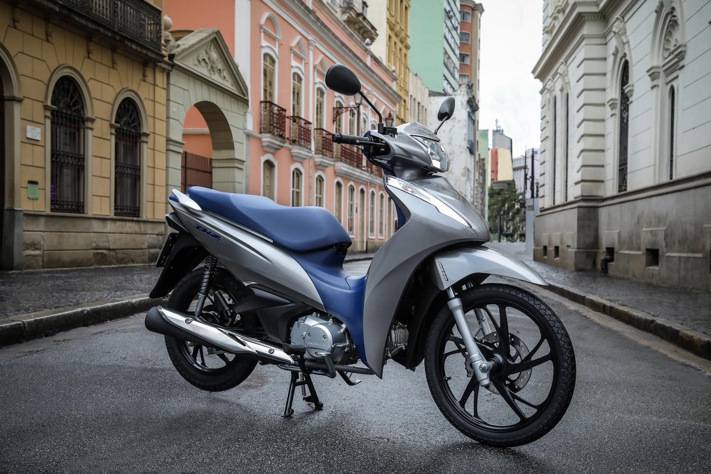 Scooter estático na cor prata metálico com banco e parte da carroceria azul