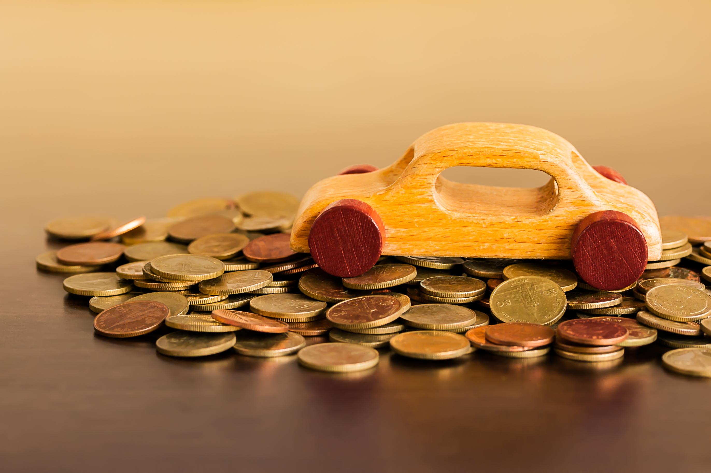 Imagem de um carro de madeira de brinquedo em cima de uma pilha de moedas