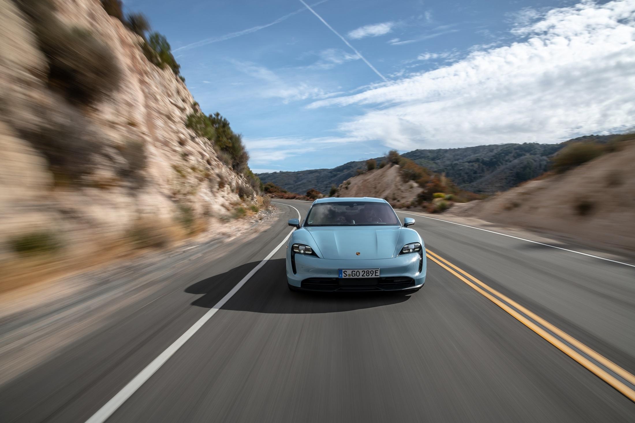 Porsche Taycan 4s na cor azul em movimento de frente na estrada