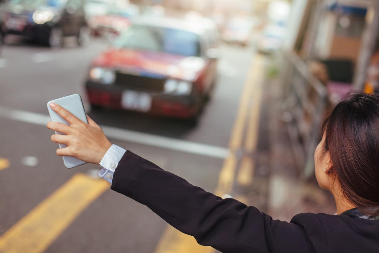 Mulher na rua com celular na mão chama carro de aplicativo