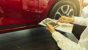 Homem segura uma calculadora e um bloco de notas em frente a um carro vermelho